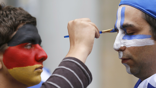 An artist with the German national colors on his face paints the Greek colors on a soccer fan in Gdansk, Poland, on Friday as Germany and Greece prepared to play in the quarterfinals of the Euro 2012 soccer championship. (AP)