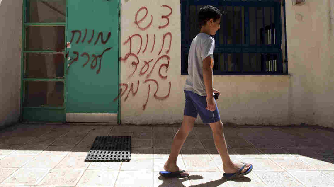 "A boy walks past spray-painted graffiti that reads in Hebrew, ""Death to Arabs"" and ""Revenge."" The vandalism took place earlier this month in the mixed Arab-Jewish community of Neve Shalom in Israel."