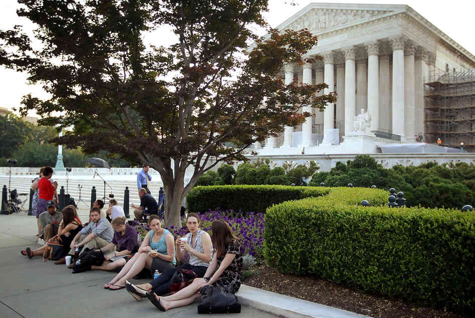 People wait outside the Supreme Court last week for word on the