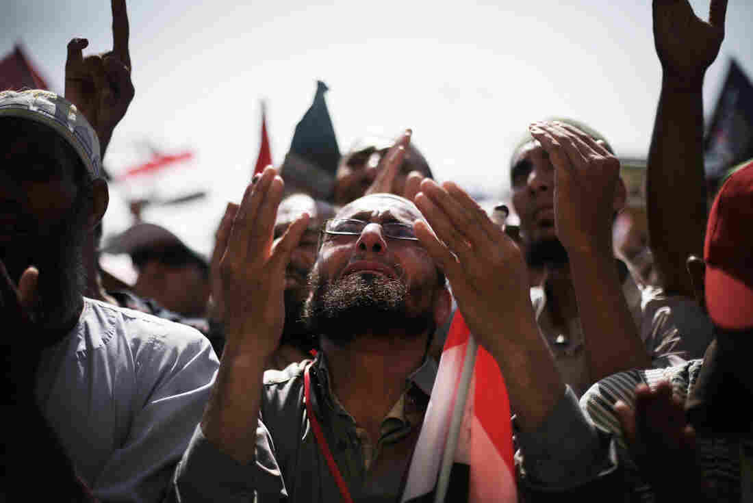 Egyptians raise their hands for prayer as they celebrate the victory of Mohammed Morsi in the presidential election in Tahrir square, Cairo, Egypt, Sunday.