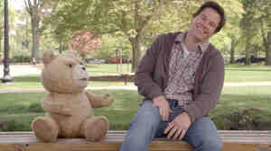 Ted (voiced by writer-director Seth MacFarlane) and Johnny (Mark Wahlberg) share a laugh in Ted. The talking teddy bear got his powers when 8-year-old Johnny wished upon a falling star for Ted to speak.