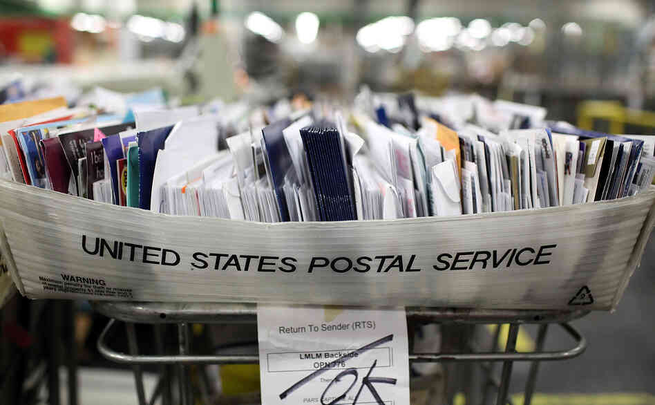 Cartons of mail ready to be sorted sit on a shelf at the U.S. Post Office sort c