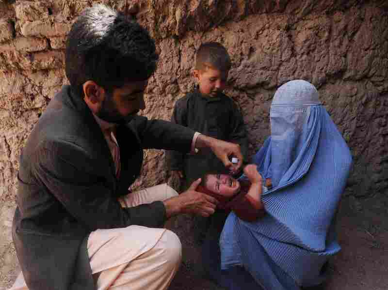 Many Afghan government programs depend on foreign aid. Here, an Afghan health worker administers a polio vaccine to a child in the western province of Herat on March 27.