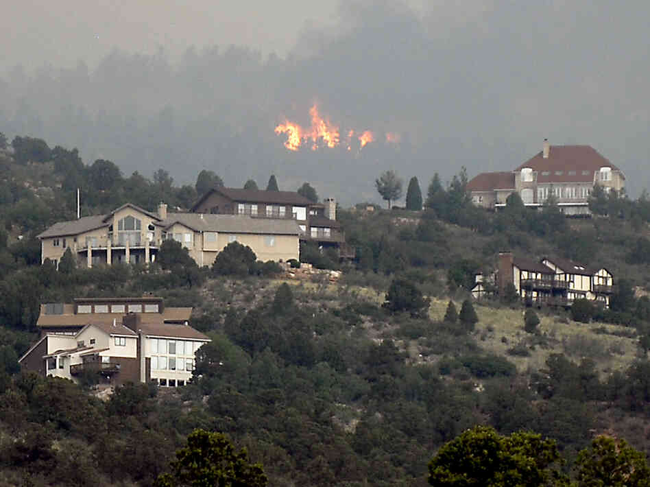 A wildfire burns near houses outside Colorado Springs, Colo., Sunday, when the fire grew to more than three s