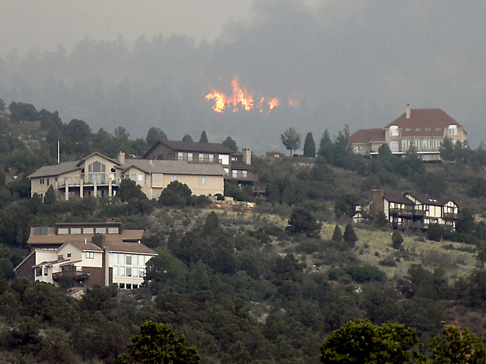 A wildfire burns near houses outside Colorado Springs, Colo., Sunday, when the fire grew to more than three square miles. More than 11,000 residents have been evacuated.