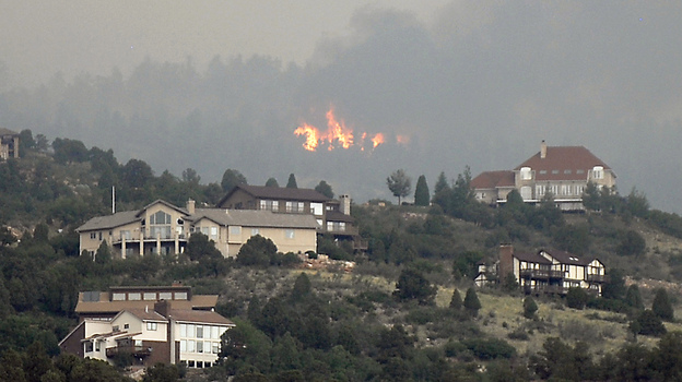 A wildfire burns near houses outside Colorado Springs, Colo., Sunday, when the fire grew to more than three square miles. More than 11,000 residents have been evacuated. (AP)