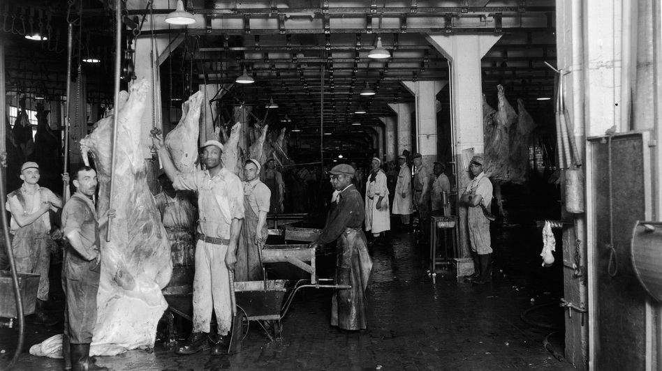 Men at a slaughterhouse stand near hanging beef carcasses, late 1940s. (Getty Images)
