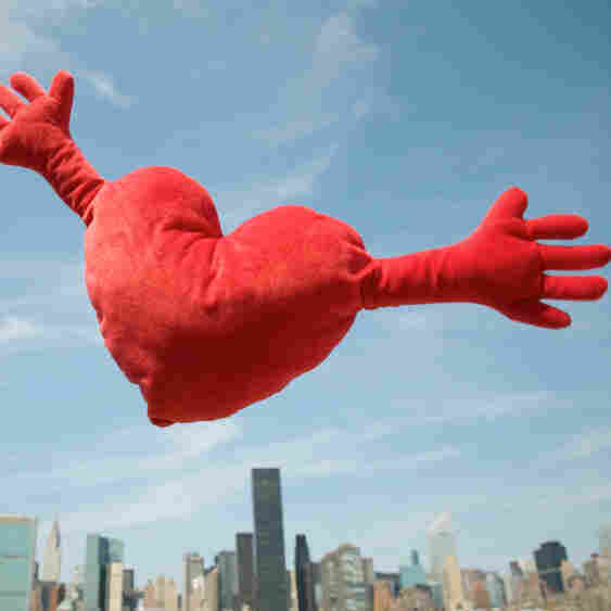 Red heart cushion with arms flies over city skyline with arms wide open for a big hug.