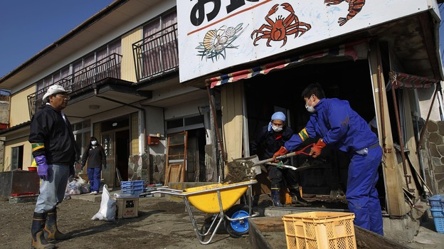 Markets in the port city of Soma, in Fukushima, Japan, are once again selling local seafood. In this file photo, volunteers help clean up a Somaseafood restaurant damaged in last March's tsunami and earthquake. (AP)