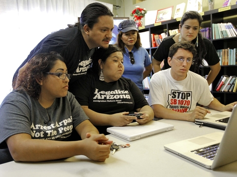 Members of the Puente Movement follow the Supreme Court's ruling on the Arizona immigration law from their office in Phoenix.
