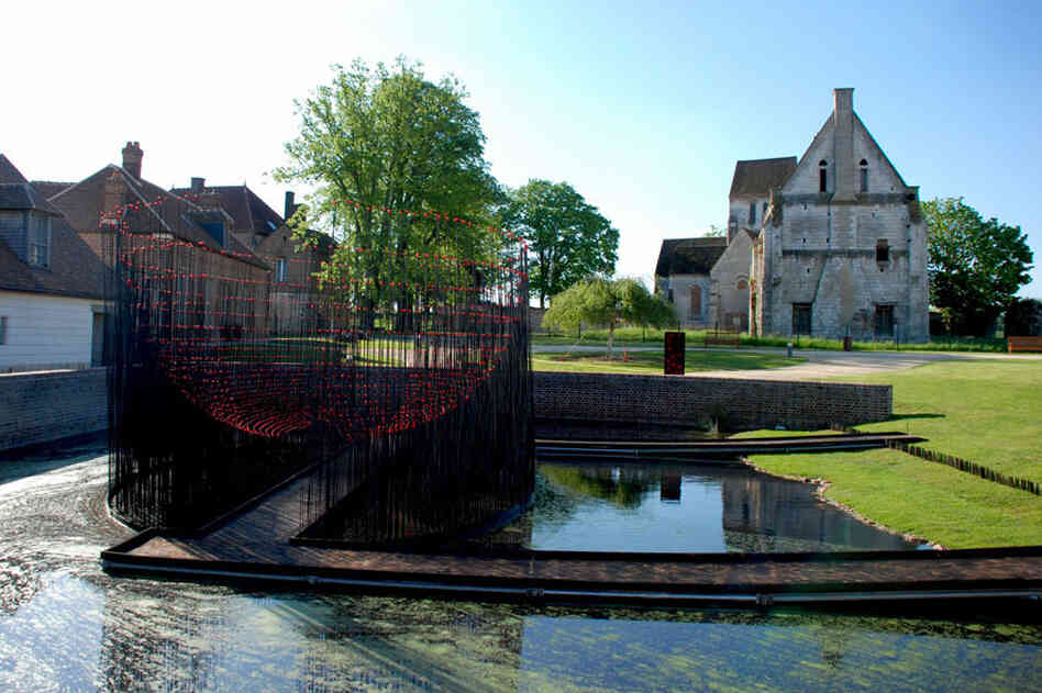 Andy Cao and Xavier Perrot's Red Bowl installation in Beauvais, France, allows visitors to cross a pond into a hemisphere of metal rods topped with red marbles.