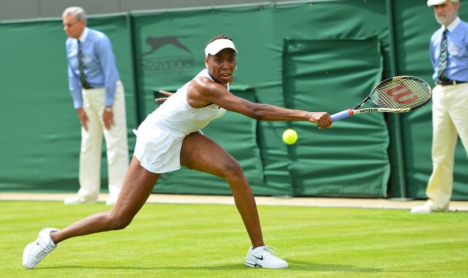 Venus Williams stretches for a return in her first-round defeat to Russia's Elena Vesnina on the first day of the Wimbledon Championships. For Williams, 32, it was her earliest exit from Wimbledon in 15 years.