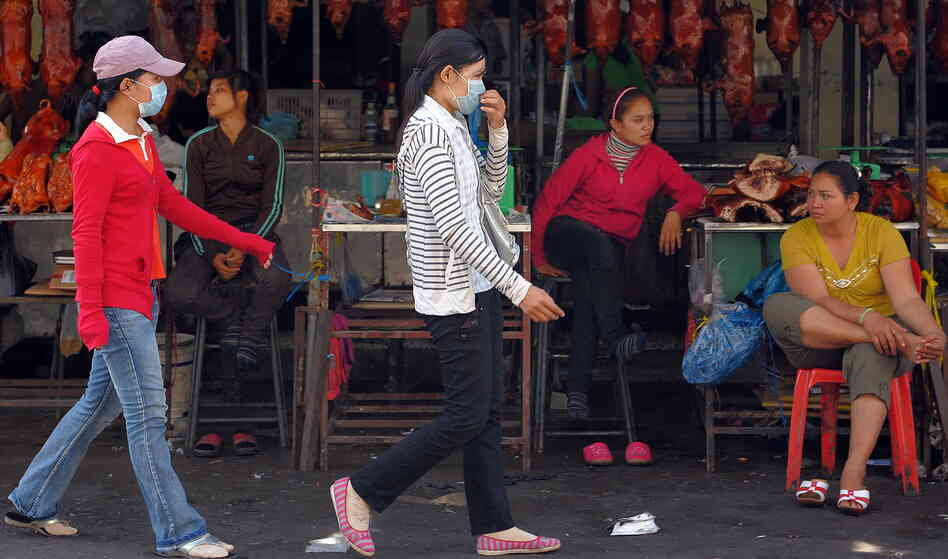 Cambodian women wear masks as they walk in a market in Phnom Penh in Oct. 2009. That month a second Cambodian died from swine flu, health officials said.