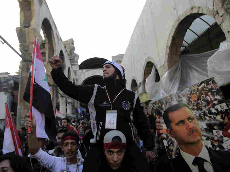 Assad supporters chant pro-government slogans as they rally in Hamidiyah Jan. 10. But that support is crumbling, evidenced by a strike by the market's merchants to protest killings in Houla, Syria.
