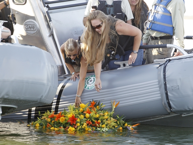 Tiffany Hartley (left) and family members lay a wreath near where her husband, David, was shot on Falcon Lake in 2010. Authorities say the shooting was the work of a Mexican drug cartel. David's body has never been found.