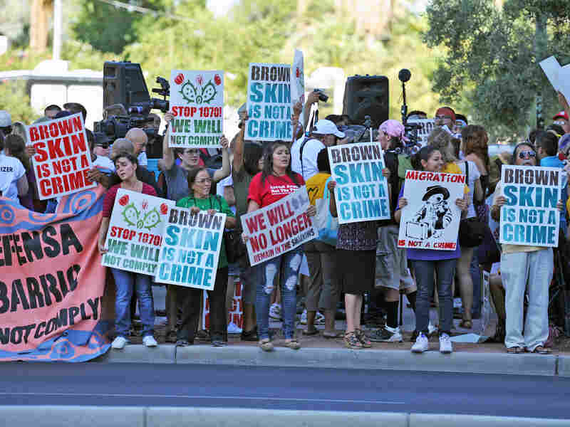 Demonstrators line the curb in reaction to the U.S. Supreme Court's decision on Arizona's immigration law, near the Immigration and Customs Enforcement offices in Phoenix on Monday.