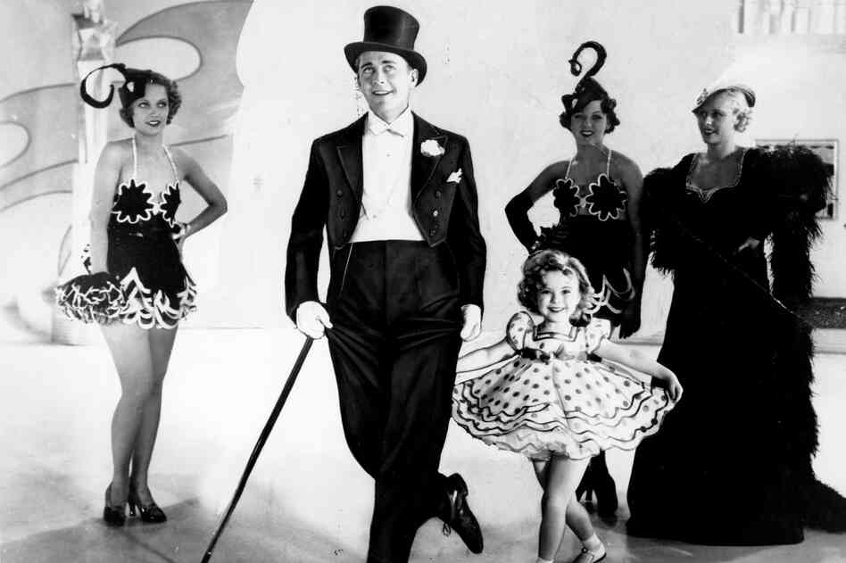 Temple curtsies in a promotional photo for the musical Stand Up and Cheer with James Dunn in 1934.
