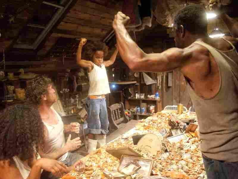 "Much as playwright Lucy Alibar's father once did, Hushpuppy's father, played by Dwight Henry (right), encourages his daughter (Wallis) to be tough and strong by saying things like, ""Show me your guns."""
