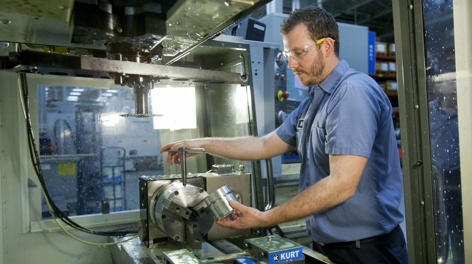 Brian Gasiewski removes the external housing for an industrial shock absorber from a CNC, or computer numerical control, machine at Fitzpatrick Manufacturing Co. in Sterling Heights, Mich. (AP)
