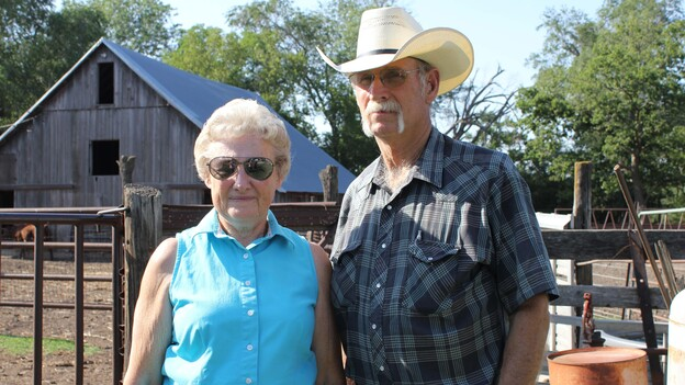 Barbara and Norman Roux stand in front of cattle pens on their farm outside of Moundridge, Kan., where she has raised cattle for nearly 70 years. (Harvest Public Media)