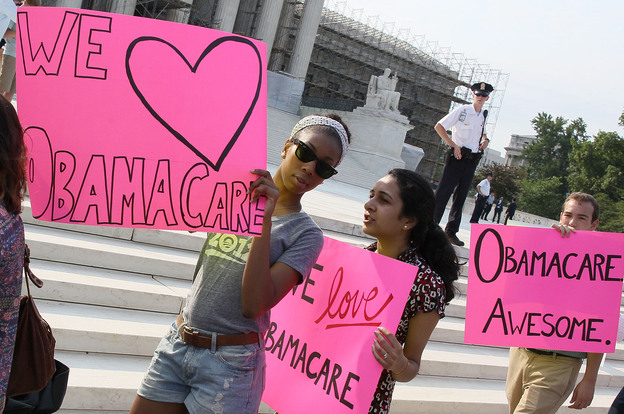 Supporters of the health care law march in front of the Supreme Court building. (Getty Images)