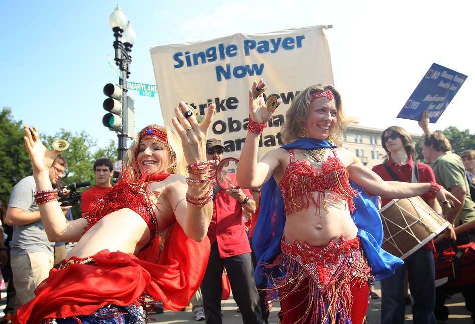Two supporters of the law belly-dance as they demonstrate in front of the Supreme Court. (Getty Images)