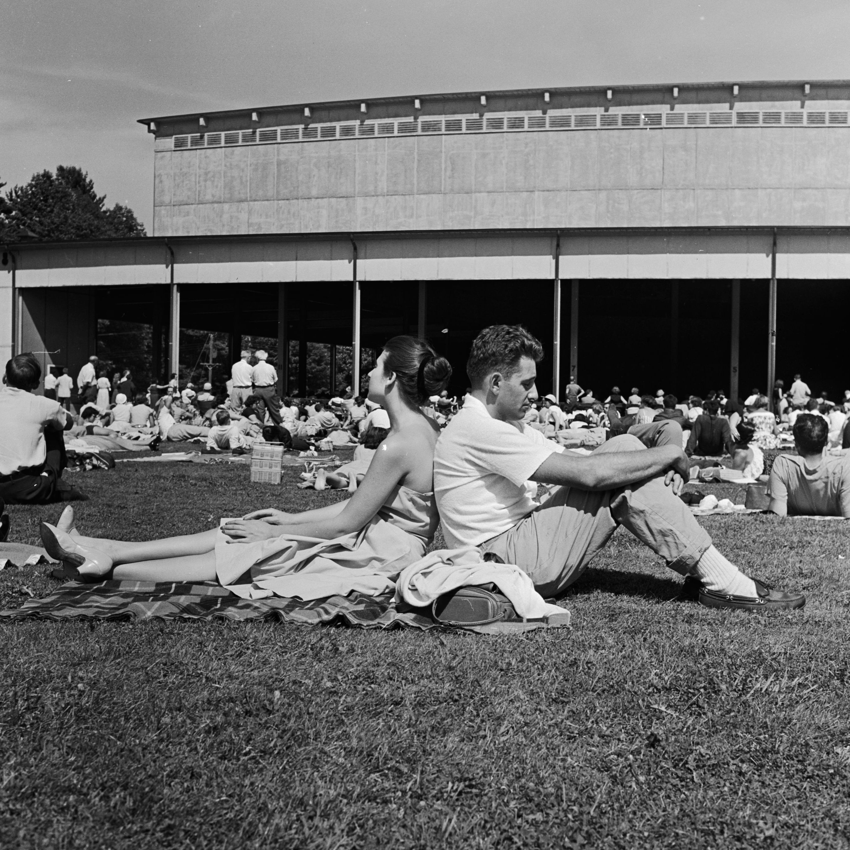 A couple seated on Tanglewood's lawn listens to the Boston Symphony Orchestra play Brahms, circa 1960.