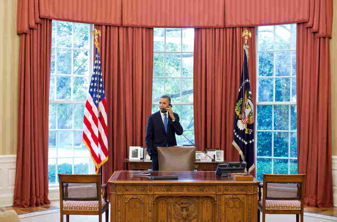 """President Barack Obama talks on the phone with Solicitor General Donald Verrilli in the Oval Office, after learning of the Supreme Court's ruling on the """"Patient Protection and Affordable Care Act,"""" on Thursday."""