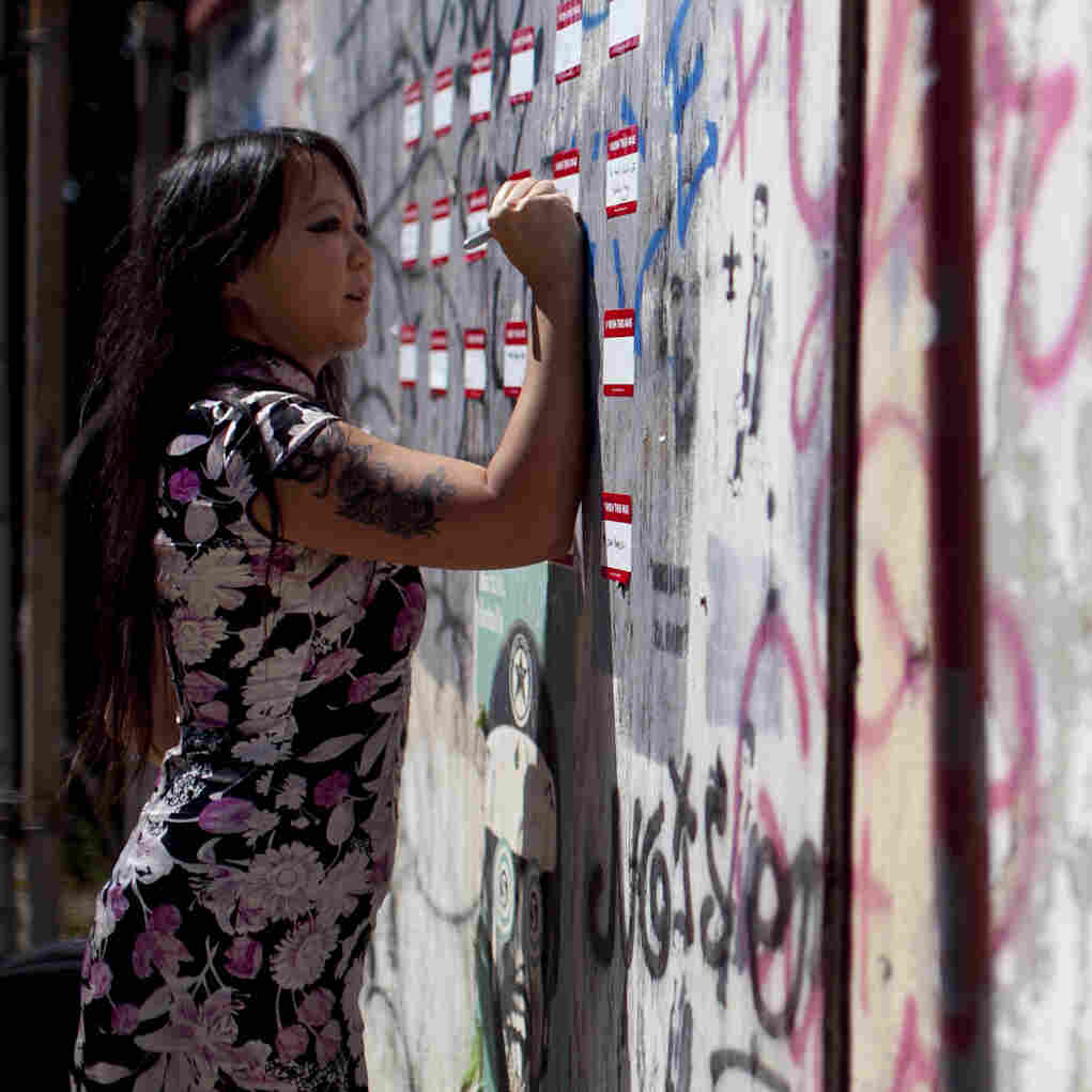 Candy Chang, co-founder of the website Neighborland, writes on an art installation in New Orleans in April. As part of a public street art project that later became Neighborland, Chang put nametag-like stickers on empty New Orleans storefronts for residents to write ideas for improving the city.