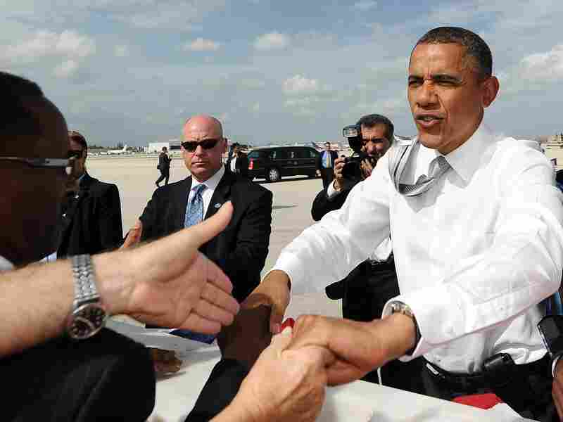 President Barack Obama greets supporters upon arriving at Miami International Airport in Miami, Fla., on June 26. Obama hit the campaign trail this week, shadowed by a week of fateful events at home and abroad weighing heavily on his hopes of re-election.