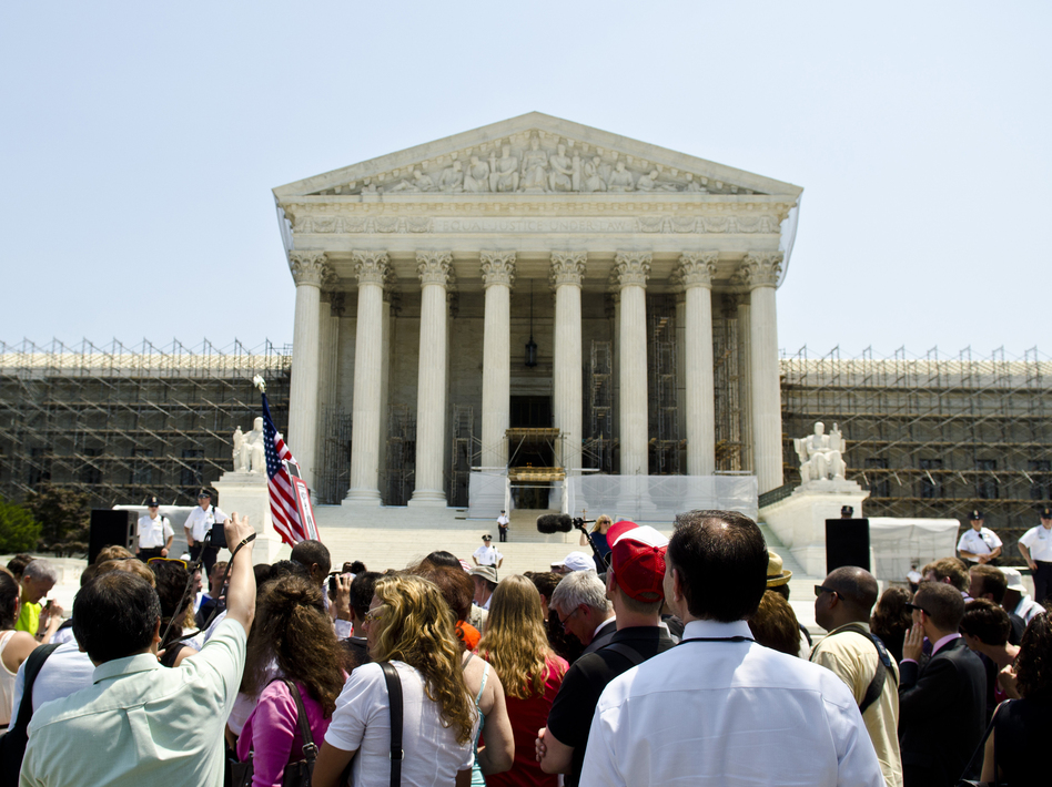 Protesters stand outside the U.S. Supreme Court on Thursday. The court's ruling upholding the federal health care law is expected to have wide-reaching implications for businesses.