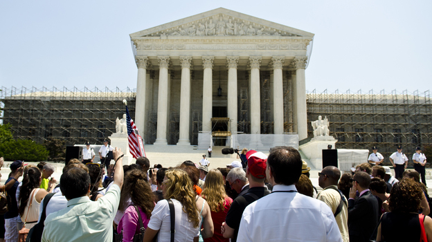 Protesters stand outside the U.S. Supreme Court on Thursday. The court's ruling upholding the federal health care law is expected to have wide-reaching implications for businesses. (Getty Images)