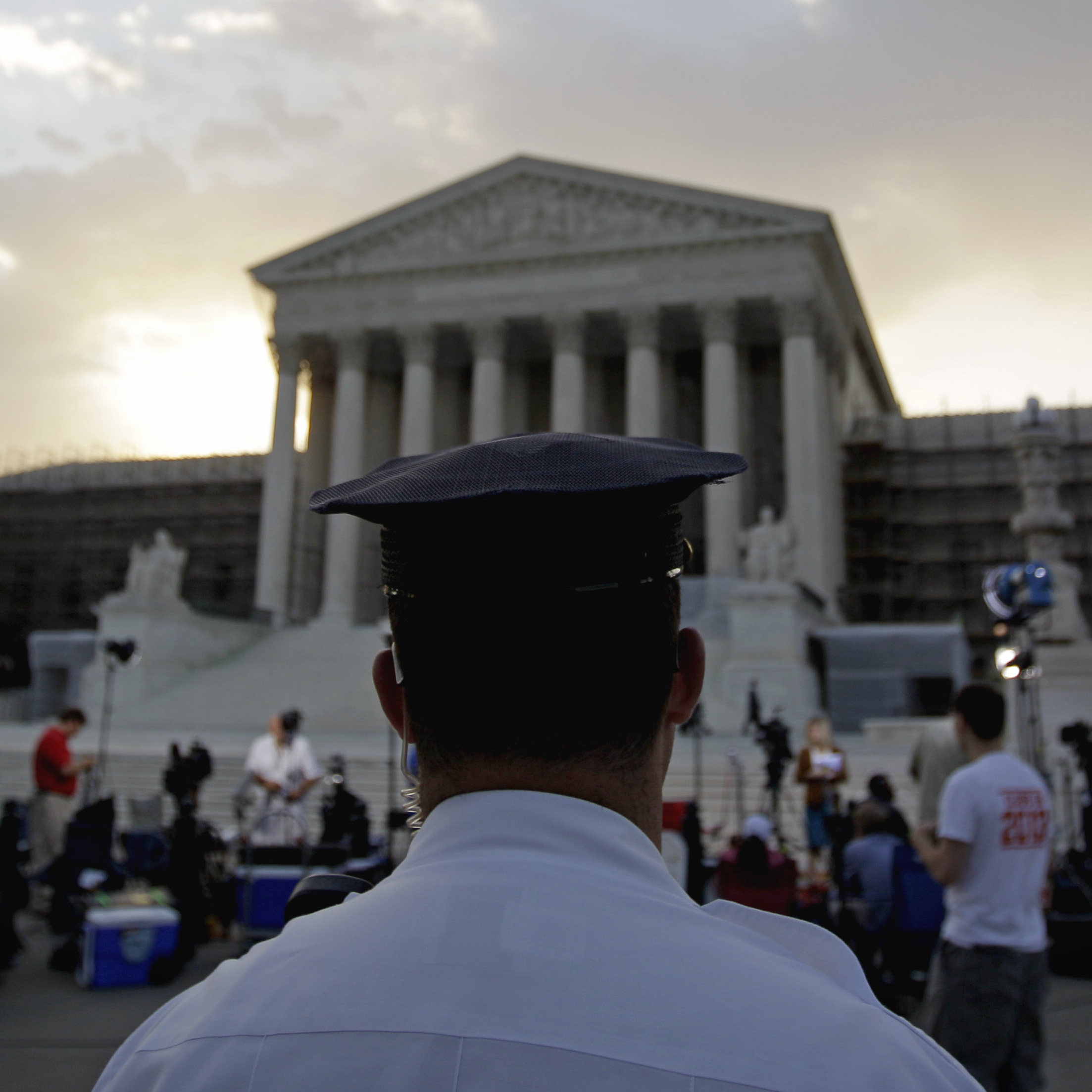 An officer stands outside the Supreme Court as media and the public gather Thursday.