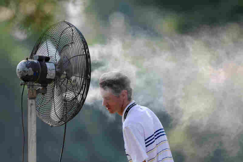 A spectator cools off with a spray mist during first round play Friday at the AT&T National at Congressional Country Club in Bethesda, Md.