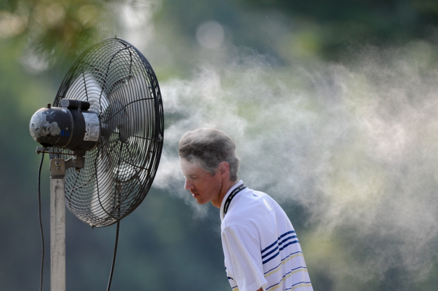 A spectator cools off with a spray mist during first round play Friday at the AT&T National at Congressional Country Club in Bethesda, Md.  (CSM /Landov)
