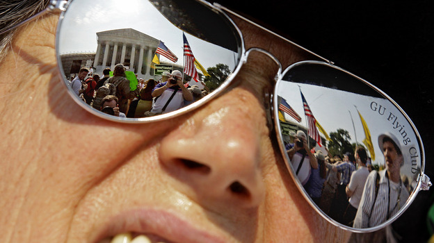 The Supreme Court is reflected in the sunglasses of Susan Clark on Thursday as she demonstrates against President Obama's health care law. (AP)
