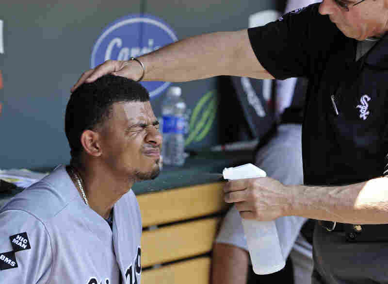 Chicago White Sox' Eduardo Escobar closes his eyes as trainer Herm Schneider sprays him with cool water during a baseball game against the Minnesota Twins in Minneapolis on Wednesday.