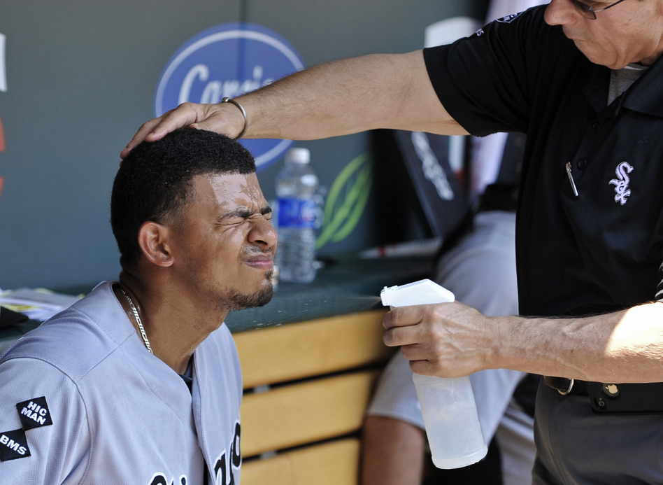 Chicago White Sox' Eduardo Escobar closes his eyes as trainer Herm Schneider sprays him with cool water during a baseball game against the Minnesota Twins in Minneapolis on Wednesday. (AP)