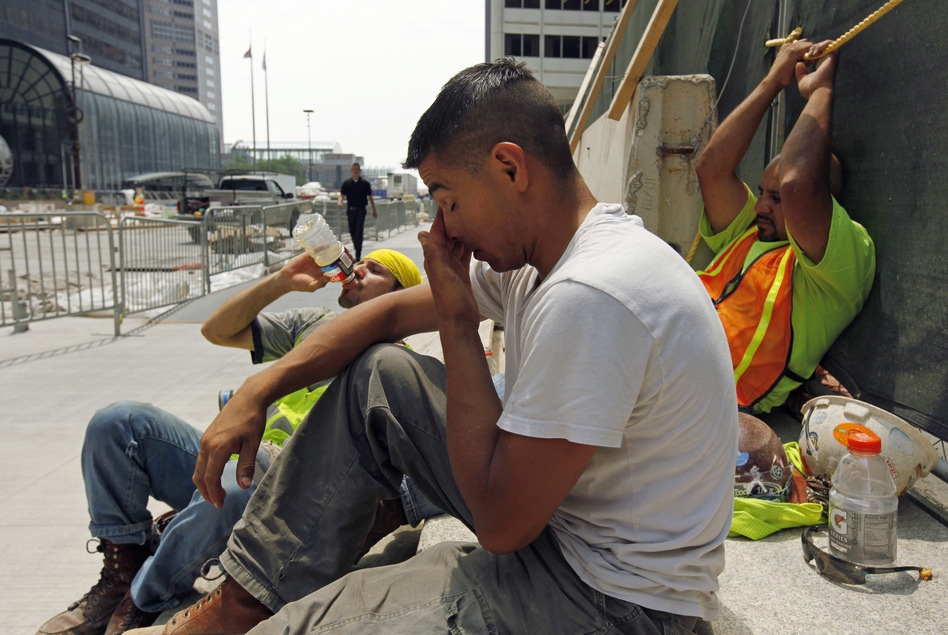 From left, construction workers Santiago Gomez, Jorge Moreno and Abel Lozano take a break from the extreme heat during a road construction project in downtown Chicago, Thursday. Little relief from the heat is expected in the next few days. (AP)