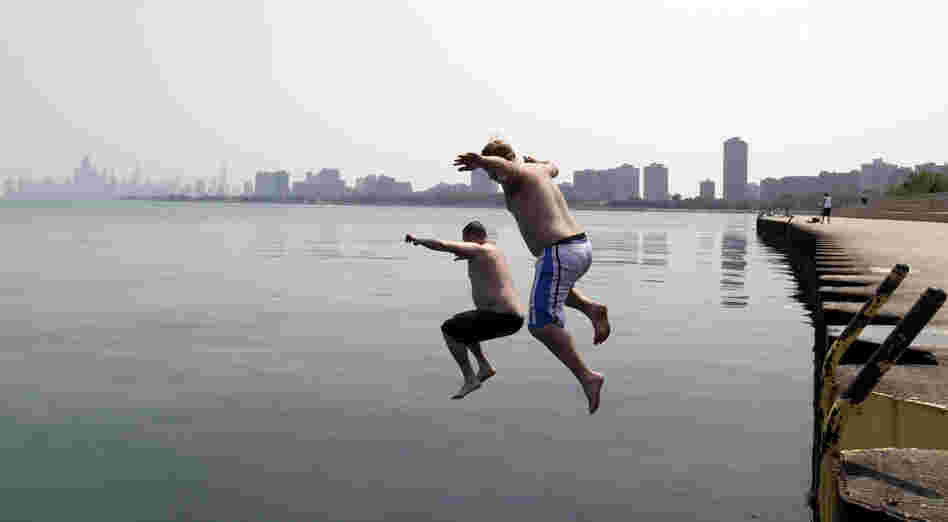 Jason Gerald (left) and Adam Hoffman jump into the Lake Michigan at Montrose Beach in Chicago on Thursday.
