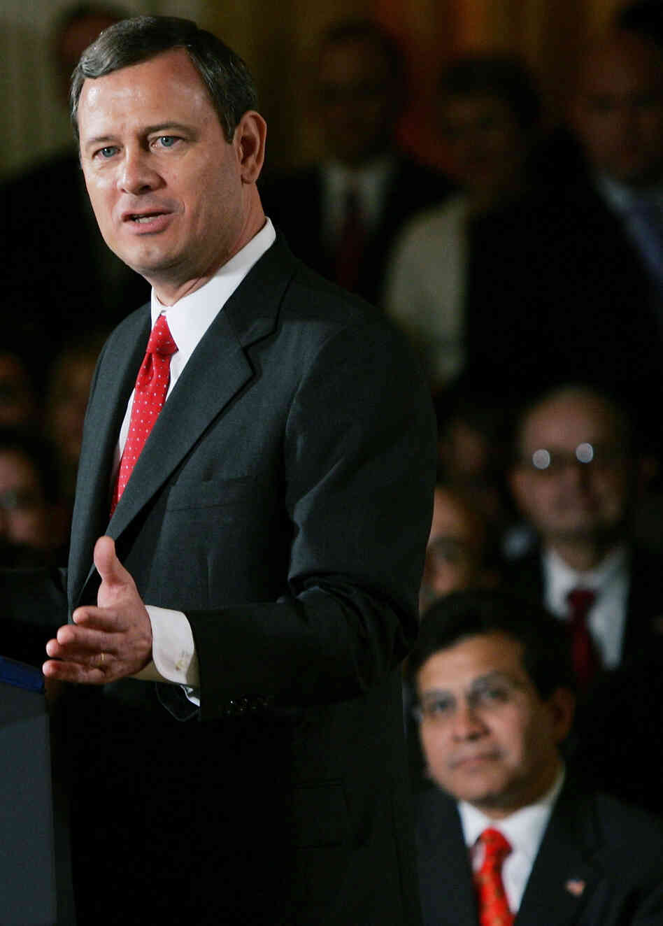 Sept. 29, 2005: Then-Attorney General Alberto Gonzales, at lower right, watches as Supreme Court Chief Justice John Roberts speaks after being