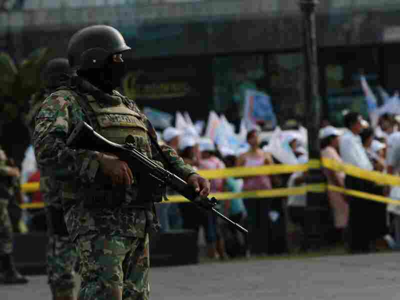 A member of the Mexican Navy stands guard in an electoral rally of Mexican presidential candidate for the National Action Party (PAN), Josefina Vazquez Mota, in Veracruz, Veracruz State, on June 24. Mexicans will go on Sunday to vote, in some areas under a virtual state of war and escorted by masked military men in full daylight.