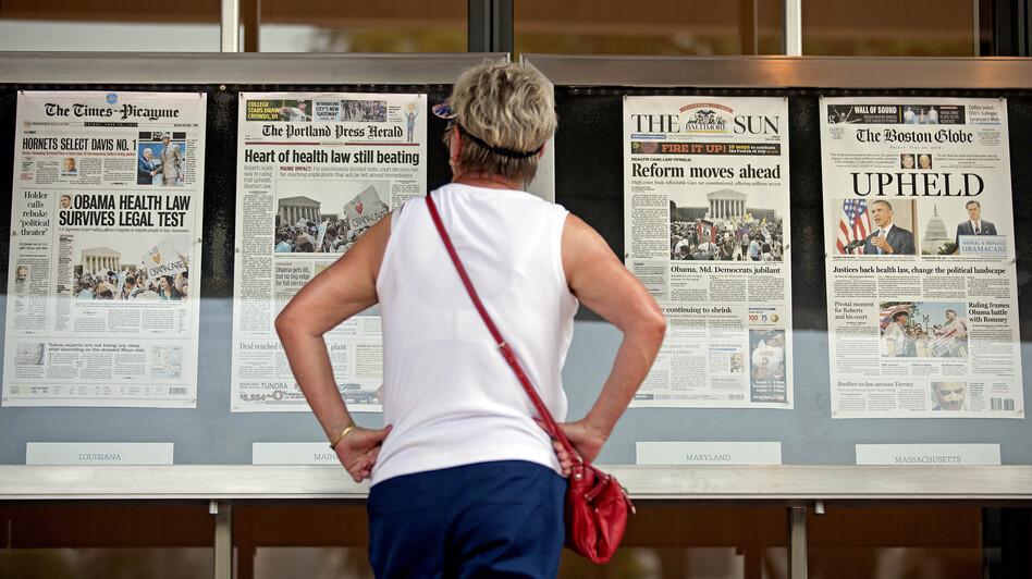 Joy Reynolds of San Diego, Calif., looks over Friday's front pages on display at the Newseum in Washington, the day after the Supreme Court ruling on President Barack Obama's health care law.