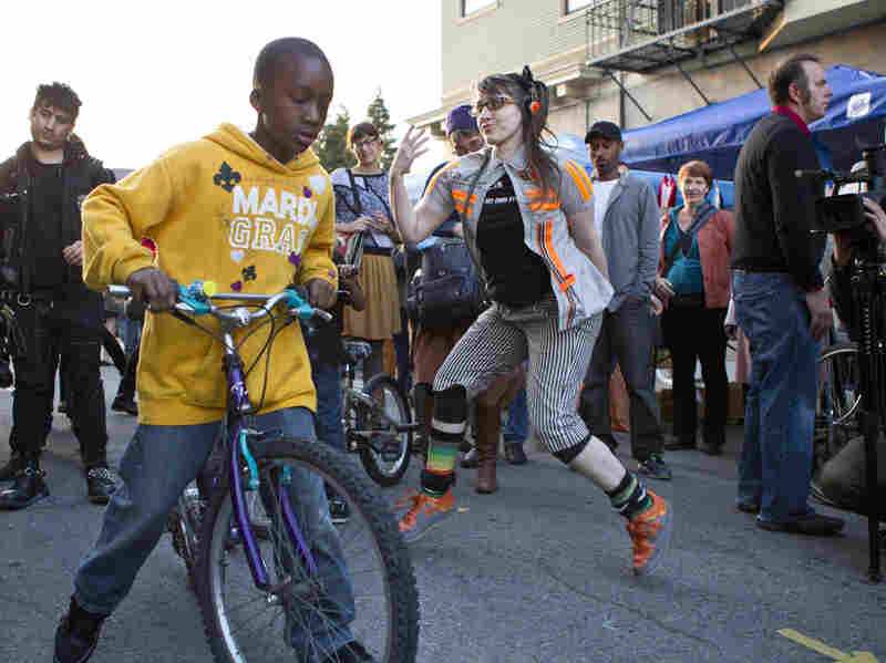 A performance artist dances on 23rd Street in Oakland as First Friday Art Walk attendees pass by.
