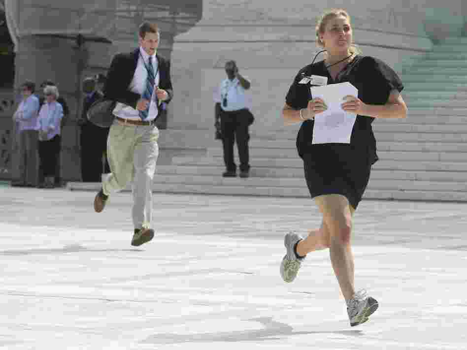 Reporters sprint from the Supreme Court after a majority of the justices upheld the constitutionality of the Affordable Care Act.
