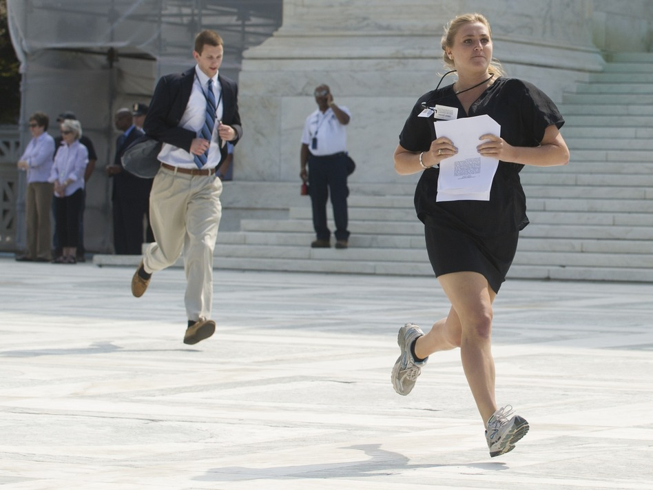 Reporters sprint from the Supreme Court after a majority of the justices upheld the constitutionality of the Affordable Care Act. (AFP/Getty Images)