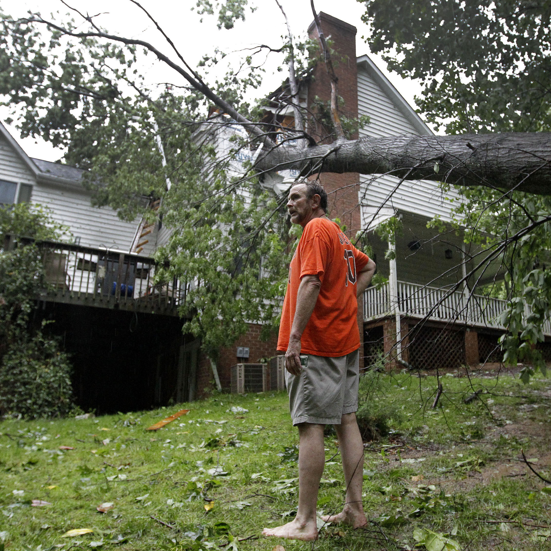 Doug Swinton surveys his property after a tree fell through his home's roof in Gamber, Md., Saturday.