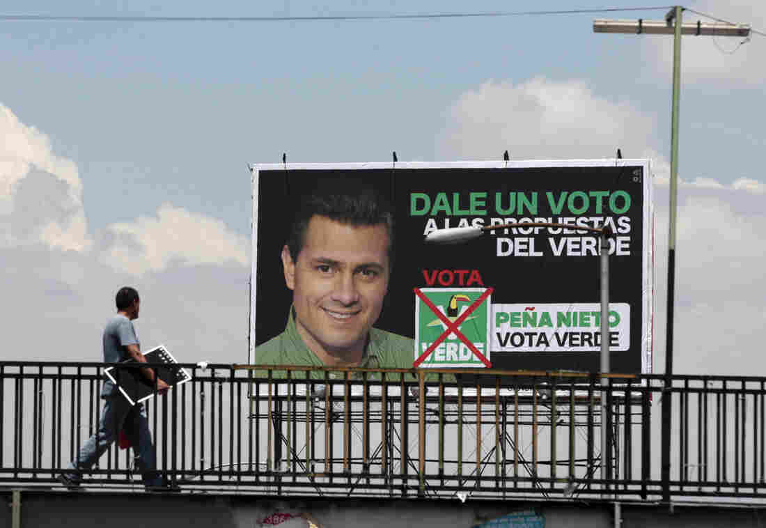 A man walks past a campaign sign for Enrique Pena Nieto, of the opposition Institutional Revolutionary Party. Mexicans vote for their next president on Sunday.