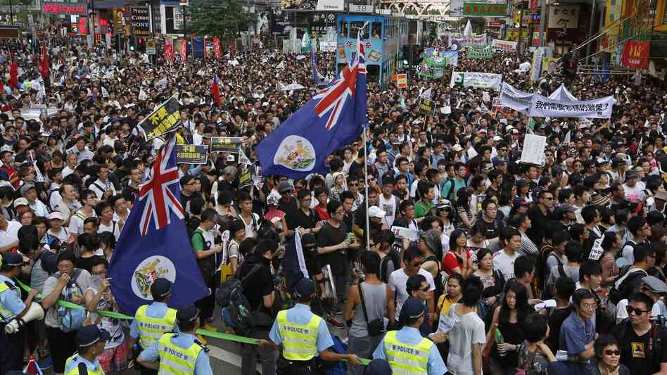 Flags from Hong Kong's colonial period fly over crowds in Victoria park on Sunday.Huge crowds pack Hong Kong's Victoria park, marching through the city's streets Sunday to express their dissatisfaction with the new leader.