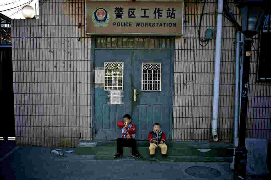 """Two small boys playing outside a local police station."""